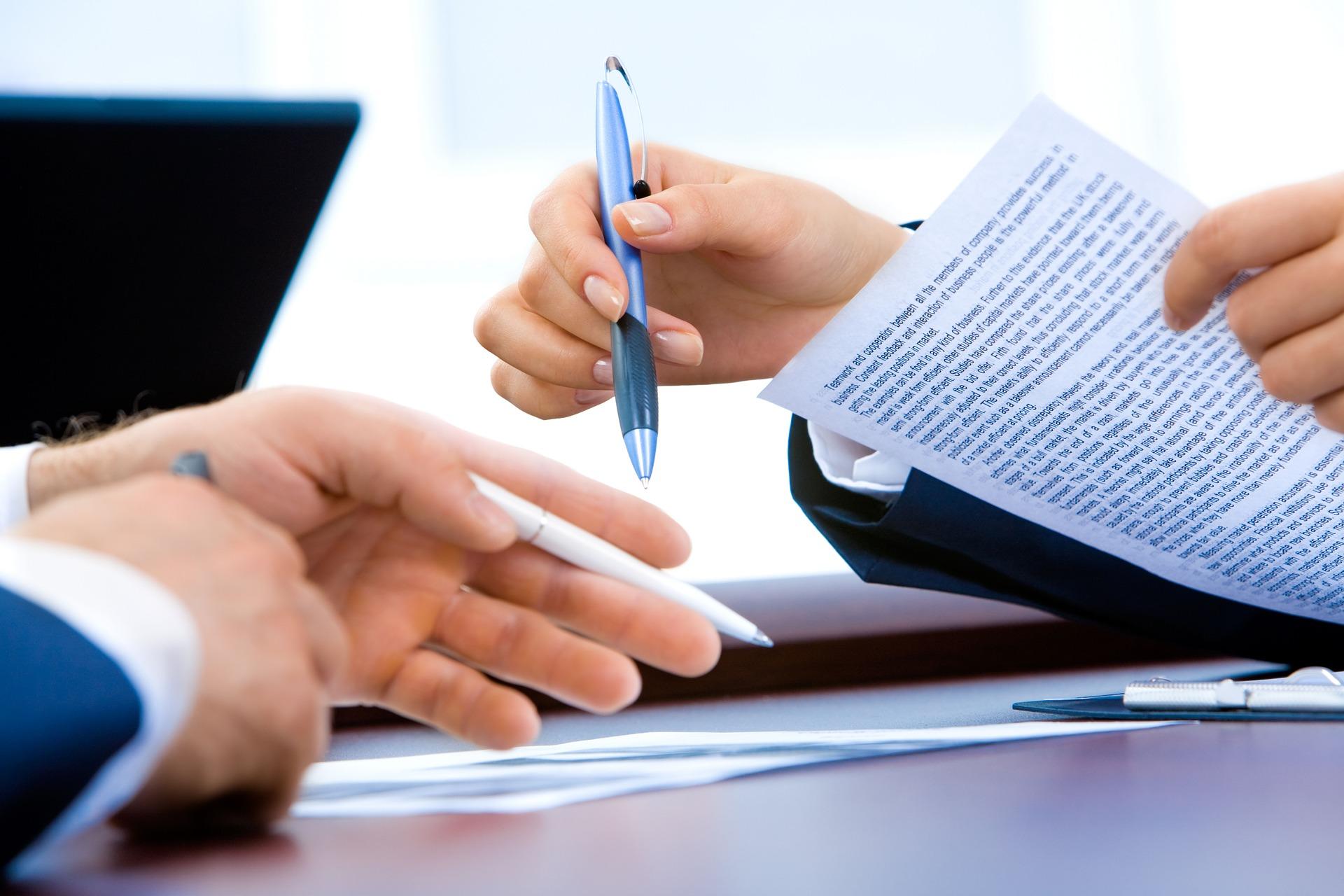 dos personas firmando documento